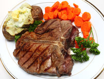 T-bone steak horizontal from above. A porterhouse (or T-bone) steak served with baked potato and boiled carrots, viewed from above royalty free stock image