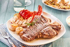 T bone steak and lobster plate. Well done style T bone steak and lobster plate on table beside roasted vegetables side dish and glass of water Royalty Free Stock Photography