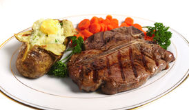T-bone steak meal horizontal. A porterhouse (or T-bone) steak served with baked potato and boiled carrots, viewed from above Stock Image