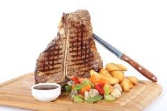 T-Bone-Steak mit garniture auf hölzerner Platte stockbild