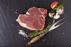 T-bone steak. A prepared piece of fresh raw T-bone steak decorated with herbs and fork Royalty Free Stock Image