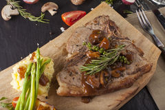 T-bone steak. A prepared piece of grilled T-bone steak brown sauce with mashed potato and vegetable on dining table with red wine decorated Royalty Free Stock Images