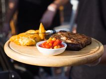 T-bone steak rare with potatoes and sauce on a wooden tray. royalty free stock image