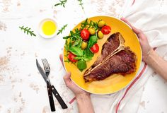 T-bone steak ready to eat, served on a plate, view from above. T-bone steak cooked and ready to eat, served on a plate, overhead view Royalty Free Stock Image