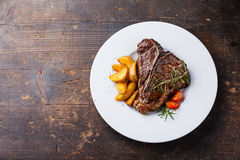 T-Bone Steak with roasted potato wedges. On white plate on wooden background Royalty Free Stock Photo