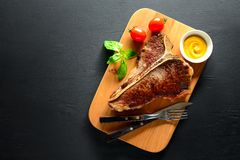 T-bone steak served and ready to eat. Cooked and ready to eat T-bone steak served on a board, flat lay, view from above, space for a text Stock Photo