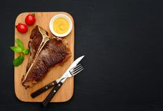 T-bone steak served and ready to eat. Cooked and ready to eat T-bone steak served on a board, flat lay, view from above, space for a text Royalty Free Stock Photography