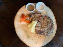 T-Bone-Steak-Spitzenteller auf einem hölzernen Schneidebrett lizenzfreies stockbild
