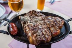 T-bone steak. On a cast-iron frying pan Royalty Free Stock Photo