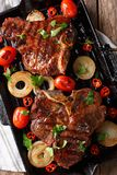 T-Bone steak with tomatoes and onions in a grill frying pan clos Royalty Free Stock Photos