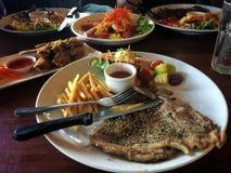 T-bone steak on white dish stock images