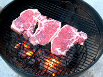 T-bone steaks on grill. Top view on three fresh raw t-bone steaks grilled on a barbecue Stock Image