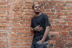 黑T恤杉的年轻可爱的深色皮肤的人在红色bricked背景 免版税图库摄影