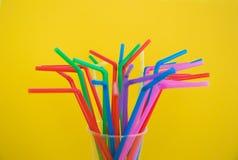 T?bulos pl?sticos multicolores para un c?ctel en un vidrio en un fondo blanco Pol?meros en vida cotidiana foto de archivo