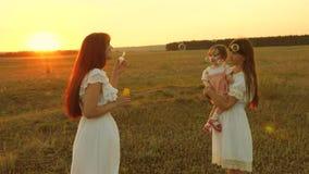 T?chter freuen sich und l?cheln, Blasen fliegen in Park bei Sonnenuntergang Langsame Bewegung Gl?ckliche Mutter, die mit den Kind stock footage