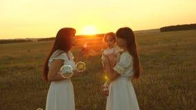 T?chter freuen sich und l?cheln, Blasen fliegen in Park bei Sonnenuntergang Langsame Bewegung Gl?ckliche Mutter, die mit den Kind stock video