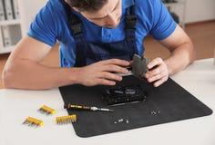 T?cnico de sexo masculino que repara el disco duro en la tabla dentro imágenes de archivo libres de regalías