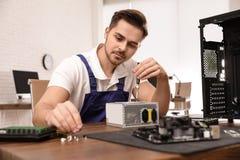 T?cnico de sexo masculino que repara la unidad de la fuente de alimentaci?n en la tabla imagen de archivo