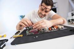 T?cnico masculino que repara o cart?o-matriz na tabela fotos de stock