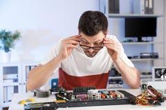 T?cnico masculino que repara o cart?o-matriz na tabela fotos de stock royalty free