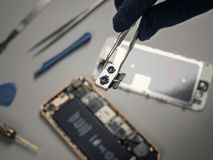 T?cnico que repara smartphone quebrado na mesa fotos de stock royalty free