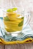 Tè con la menta e l'intero limone in una tazza trasparente Immagine Stock