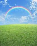 Tęcza z zielonej trawy polem nad niebieskim niebem Zdjęcia Stock