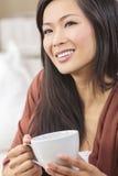 Té de consumición o café de la mujer asiática china Imagenes de archivo