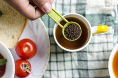 Tè della tenuta della mano del tè nero in cucchiaio della tavola Fotografia Stock