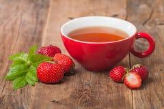 Tè di inglese nero in tazza rossa con la fragola Immagini Stock Libere da Diritti