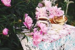 T? en estilo rural en jard?n del verano Dos tazas de t? negro y de crepes en mantel de encaje hecho a ganchillo hecho a mano del  fotos de archivo