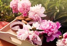 T? en estilo rural en jard?n del verano en el pueblo Dos tazas de t? negro en la bandeja de madera y las flores florecientes de l fotos de archivo libres de regalías