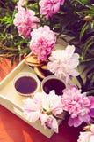 T? en estilo rural en jard?n del verano en el pueblo Dos tazas de t? negro en la bandeja de madera y las flores florecientes de l imagenes de archivo