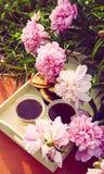 T? en estilo rural en jard?n del verano en el pueblo Dos tazas de t? negro en la bandeja de madera y las flores florecientes de l fotos de archivo
