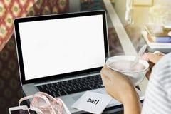Té en mano de la muchacha con el ordenador portátil de la pantalla en blanco y la cinta de la medida Imagen de archivo libre de regalías
