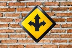 T-Kreuzung Zeichen auf Backsteinmauer lizenzfreie stockbilder