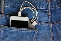 T?l?phone portable avec la batterie mobile de secours dans la poche de treillis le t?l?phone portable est puissance de transfert  photo libre de droits