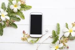 T?l?phone portable avec la composition florale sur le blanc photographie stock