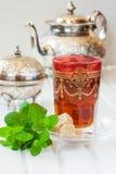 Té marroquí con la menta y el azúcar en un vidrio en una tabla blanca con una caldera Fotografía de archivo libre de regalías