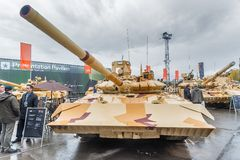 T-72. Modernized tank. Russia. Nizhniy Tagil, Russia - September 26. 2013: Visitors explore military equipment on exhibition range. Modernized tank T-72. RAE Royalty Free Stock Photography