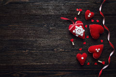 Tło z czerwonymi tkanin sercami i faborek na stary ciemny drewnianym Obrazy Stock