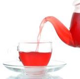 Té que es vertido en la taza de té de cristal aislada Foto de archivo