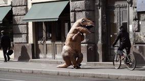 t rex服装的滑稽的人在走在城市边路的人人群  股票录像