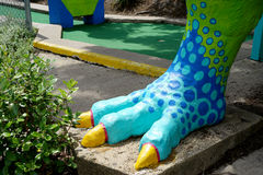 T. rex foot at miniature golf course. Tyrannosaurus rex presides over a miniature golf course in Austin, Texas. His clawed foot looks a lot like a bird foot Royalty Free Stock Photos
