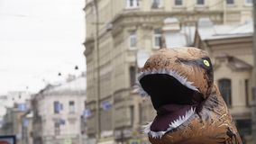 T Rex mascot costume head shaking at city street. On sunny day, busy traffic stock video
