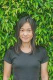 T-shirt asiatique de noir d'usage de portrait de femme de photo de pousse et sourire avec le fond vert d'arbre photo libre de droits