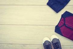 T-shirt avec le pantalon et les chaussures sur le fond en bois Photos stock