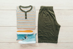 T-shirt avec le pantalon et les chaussures sur le fond en bois Photo stock