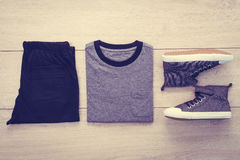T-shirt avec le pantalon et les chaussures sur le fond en bois Images stock