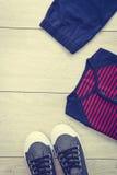 T-shirt avec le pantalon et les chaussures sur le fond en bois Photographie stock